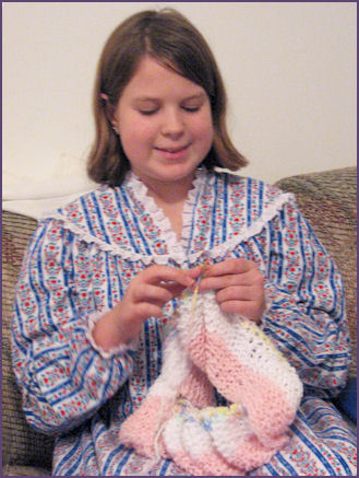 Diana, knitting a garter stitch striped baby blanket