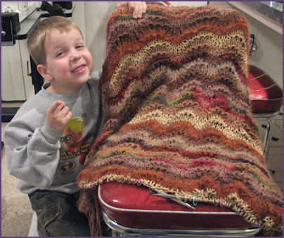 boy smiles with goofy grin, posing next to afghan in progress