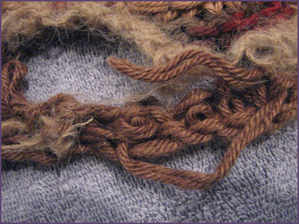 closeup of bottom edge of blanket showing yarn end sticking out