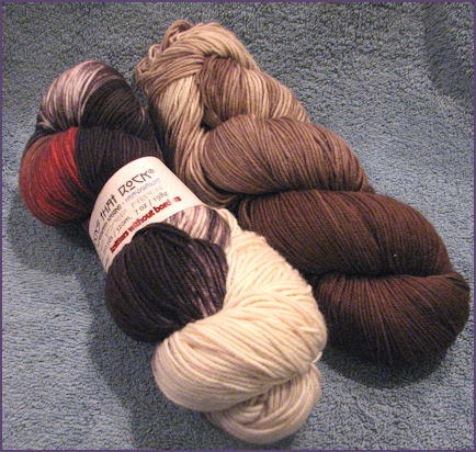 two hanks of socks that rock yarn, one in shades of brown and the other is red, black, and white