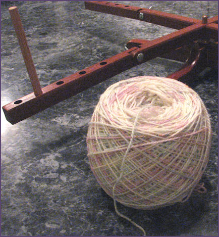 ball of yarn in foreground of photo with wooden swift in the background