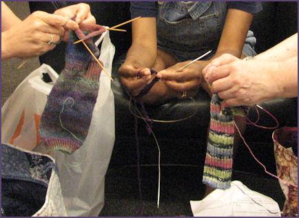 group of hands all knitting socks