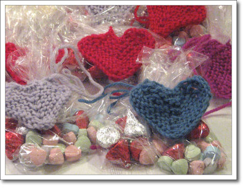 Valentine candies in baggies with knitted hearts tied around them.
