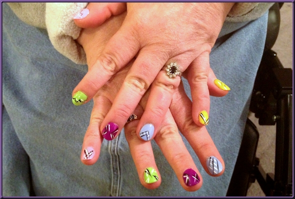 fingernails painted in various colors with black and white line designs
