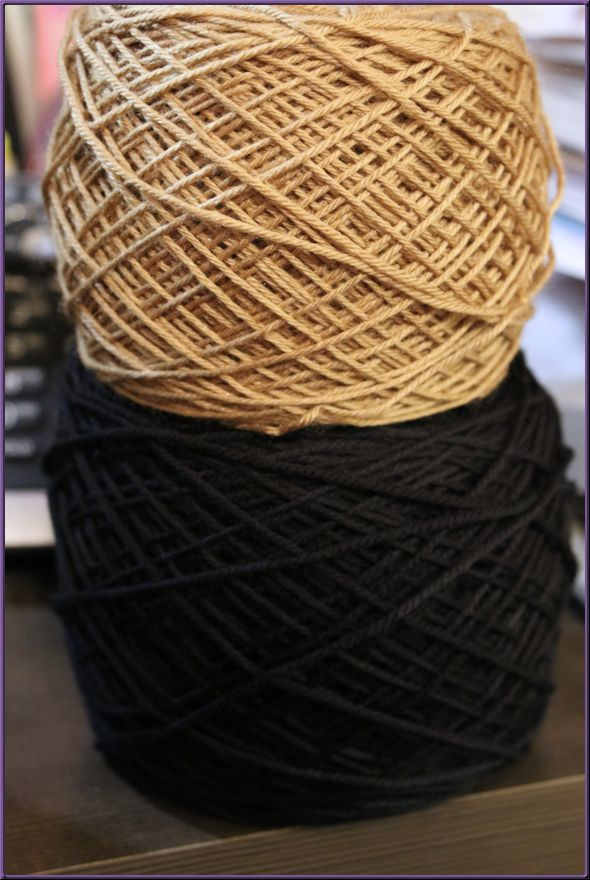 Two yarn balls, one dark green and one tan