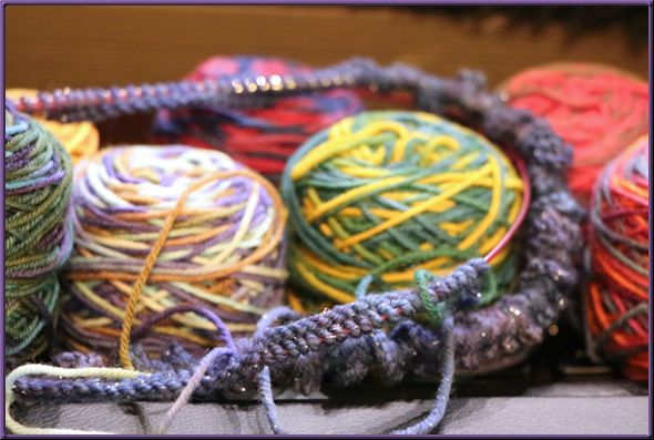 Lots of stitches cast on to the knitting needles, among a pile of small balls of yarn
