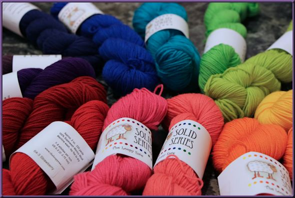 multiple skeins of yarn arranged according to the color spectrum