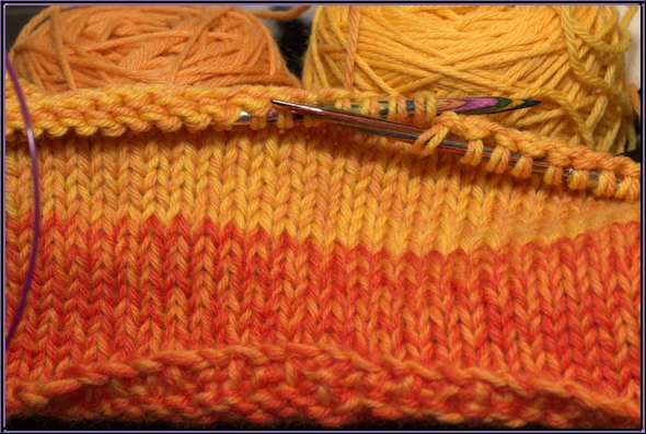 closeup of yellow and orange knitted hat in progress.