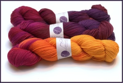 Three balls of yarn in two colorways, that go from bright yellow, to orange, to purples