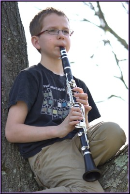 Steven, playing clarinet while sitting in his favorite tree.