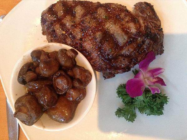 Steak and mushrooms with purple flower